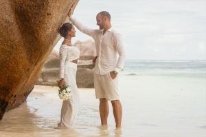 Hochzeit La Digue ganz in Weiss - Brautpaar lehnt am Felsen