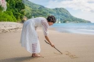 Strandhochzeit Bel Ombre Braut schreibt in den Sand