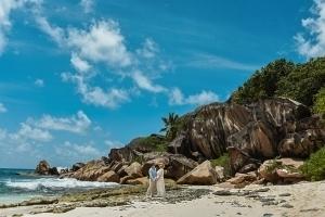 Strandhochzeit La Digue, Grand Anse Brautpaar vor beeindruckender Felsenkulisse