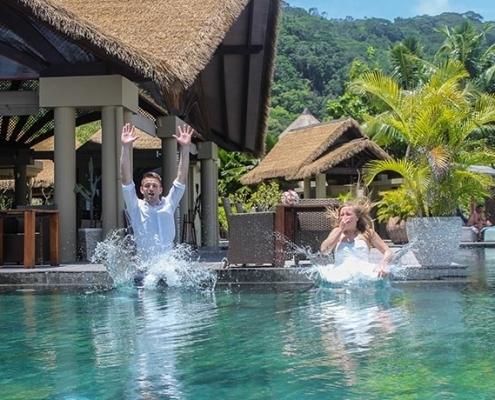 Hochzeitspaar springt in Pool