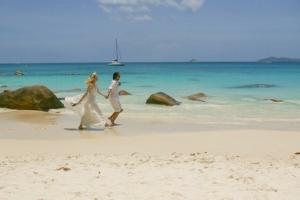 Hochzeit auf Praslin Brautpaar rennt am Strand
